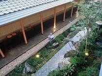 打ち水のされた石畳のアプローチ。小川には季節の花が咲き、趣のある雰囲気がございます。
