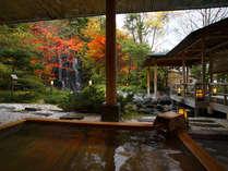 紅葉の中を流れ落ちる滝のある庭園露天風呂