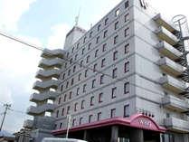 【ホテル外観】 白い建物に赤の窓枠、ピンクのエントランスが目印です。