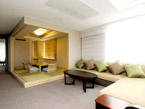 【プレミアムスイートルーム】大きなソファとゆったりした空間でお寛ぎいただけるリビング。
