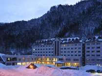 雪景色の峡谷をバックにライトアップされた朝陽リゾートホテル(12月~3月頃)