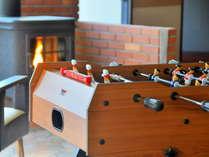 【ロビー一角の遊戯台】暖炉の前に置かれたサッカーゲーム台。どなたでもお使いいただけます。