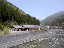 *【外観】川沿いに佇む、道の駅に併設された全9室の宿。