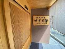 樅ノ木に書き下ろされた館名文字。大きな桧製の自動ドアがお客様をお迎えします。