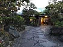 正門からのアプローチ。贅沢な石畳と松木