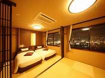 夜景側◆モダンな琉球畳の上にベッドを配した和洋室。畳のお部屋は足を伸ばして寛げる。
