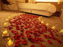 花びらとキャンドルでつくるキャンドルロードと ベッド一面に花びらを散りばめたデコレーション