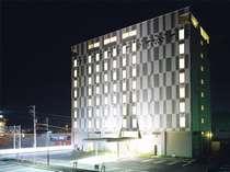 夜のホテル外観です。グレーとホワイトを基調にした10階建てのホテルです。