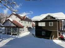 冬景色に立つプチホテルアッサムとコテージぶな。