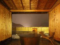 露天付客室「風人」の鋳鉄製の露天風呂です。垣根の向こうには湖が。(日没後のブルーモーメント。)