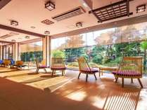 天童木工の椅子が並べられたラウンジ。ガラス越しに庭園を望む。