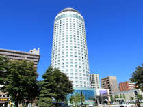 青く鮮やかな夏空の中、白い円柱形が映える札幌プリンスホテル