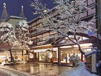 【外観/冬】冬季期間は雪吊りされた玄関前が風物詩に。雪と湯けむり香る冬の情景