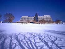 【外観】〔冬〕 銀世界に佇む、冬のウィンザーホテル。やわらかな雪が音を吸い込み、静けさに包まれます