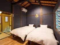 当時の屋根裏と梁が広がる寝室。オリジナルで設えた真鍮の瓢箪ブラケットが優しく照らします。