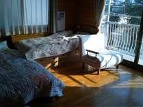 洋室10畳。シングルベット二つとソファベット一つ。