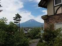 玄関横のウッドデッキにあるパラソル付のガーデンテーブル&チェアから望む夏の富士山