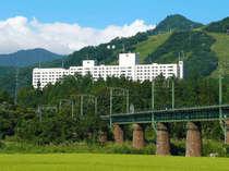 【グリーンシーズン・ホテル外観】越後の山々の囲まれた里山に位置するホテル。手前に見えるはJR上越線