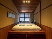 2階「八百」の弁柄色の米杉(べいすぎ)天井で落ち着いた雰囲気の洋寝室。