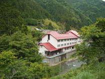 緑いっぱいの渓流沿いに立つ、ホテルのせ川