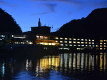 海から見た夜のシーサイドホテル。明かりが水面に反射して幻想的です。
