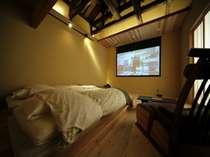古民家の梁天井を生かしたベッドルームと120インチのホームシアター設置の「金明」