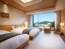 畳のお部屋にシングルベット2台と窓側にソファーセットを配置したお部屋です。