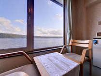 *洋室ツイン/窓辺の椅子に腰かけて、北海道の大自然を独り占め。癒しのひと時をお過ごしいただけます。