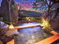 巨大岩の間から夕景パノラマを望む月の湯(貸切露天風呂)