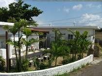 ゲストハウス 南国屋の中庭と玄関。白い建物の周りには、ハイビスカスとヤシの木で、囲まれた宿