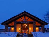 【冬の当館正面玄関】雪と光により幻想的な風景となります。