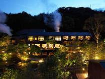 日本庭園と源泉櫓から立ち昇る湯気が、幻想的な雰囲気を演出します。