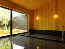 大露天風呂「風花」の内風呂、黒い浴槽と桧の壁がモダンな印象です。