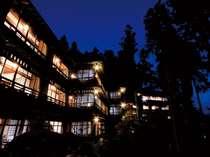下呂温泉街を望む山の中腹に佇む本館建屋の外観夜景。