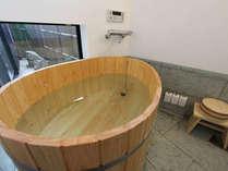 ひのき風呂と床に天然青石「十和田石」を使用した贅沢な浴室