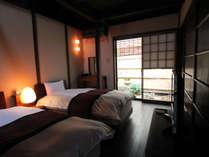 坪庭を眺める寝室。天井は京町家ならではの火袋を再現しました。チェックアウトは遅めの11時です。