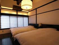 寝室にはダブルベッド2台。歴史ある梁の天井を眺めながらゆったりとお休み頂けます。