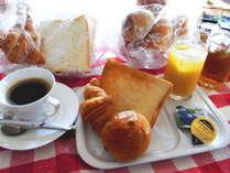 無料朝食は数種類のパンに淹れたてのコーヒー、ジュース等をご用意しております。