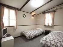 【ツインルーム】シンプルでコンパクトな客室。冷蔵庫、給湯ポットがあります。