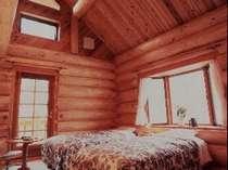 吹き抜けの天井・出窓付のお部屋。客室もログのつくりで、木のぬくもりが疲れを癒す