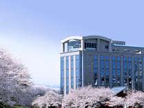 春の桜並木に面したホテル外観