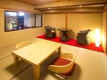 温泉露天風呂付き客室『孔雀殿・彩』のお部屋一例。座布団やソファ敷き、浴槽などにテーマ色「赤」を使用。