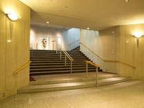 ロビー階フロント横の階段でコスモスホールに