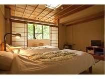 和室にベッドを配置したシンプルな客室。