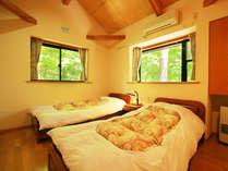 貸し別荘の二階にある寝室。木々のマイナスイオンを感じるお部屋です。
