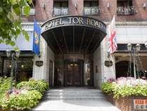 ホテルの玄関には季節を感じる花壇とユニオンジャック、レトロな回転扉があります。