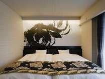 スイートルーム寝室。ゆったりサイズのセミダブルベッドを設置。全室異なる一枚絵の壁紙が目を惹きます。