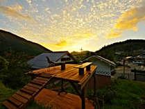 宿に併設したウッドデッキ。里山ののどかな風景と満天の星空が楽しめる。夕暮れ時もおすすめ。