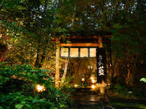 ~外門 夜~ 奥に続くアプローチの行燈がそっと覗き、幻想的にお出迎え。ゆっくりとお進みください。