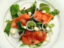 夕食、前菜一例。自家製スモークサーモンのサラダ。自家製ならではの香り高さ。